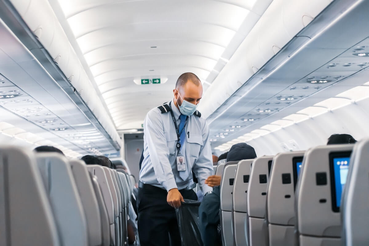 Airline attendant gathering garbage on a flight, part of post-COVID vacation safety