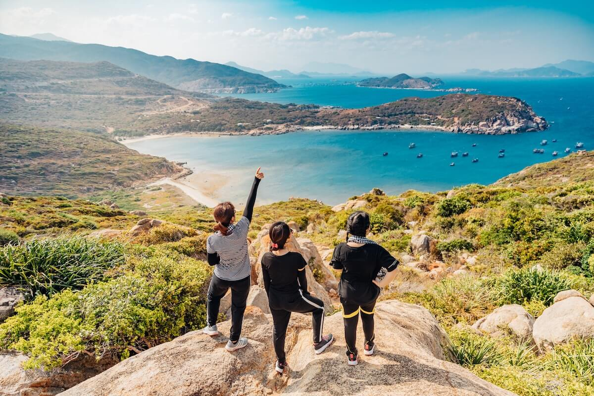 3 women overlooking a tropical coastal view