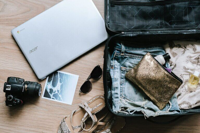 a packed suitcase, sunglasses, latop & camera, planning post-COVID vacation safety