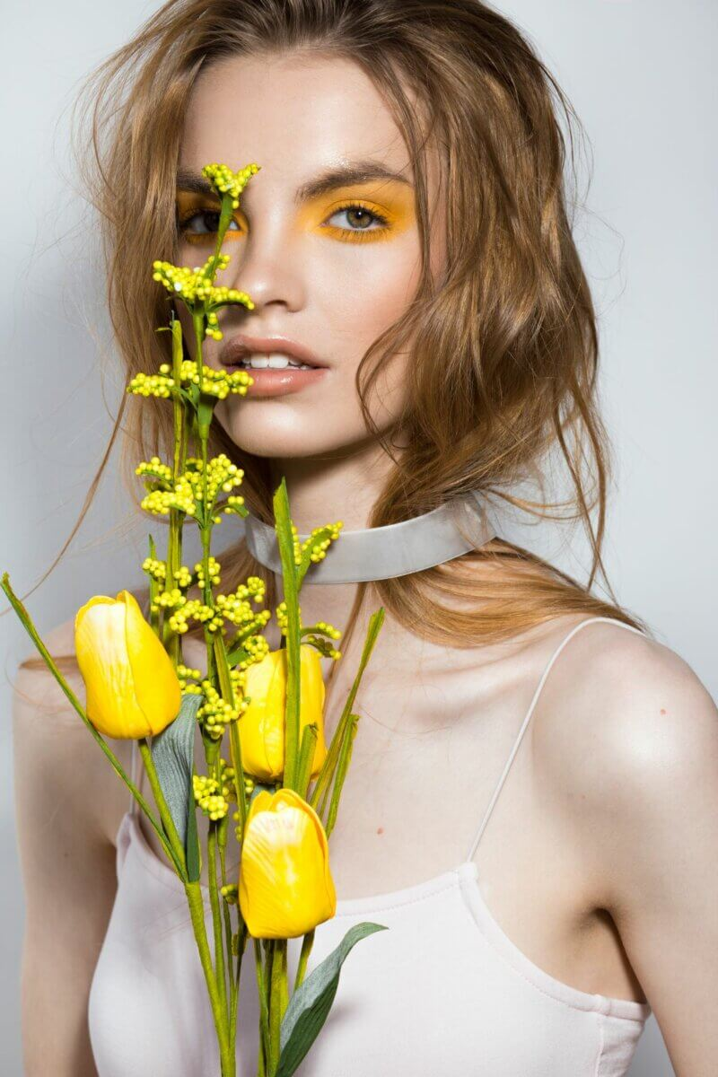 retro meets radical with a model in a pink spaghetti top, dramatic yellow eyeshadow, holding yellow tulips