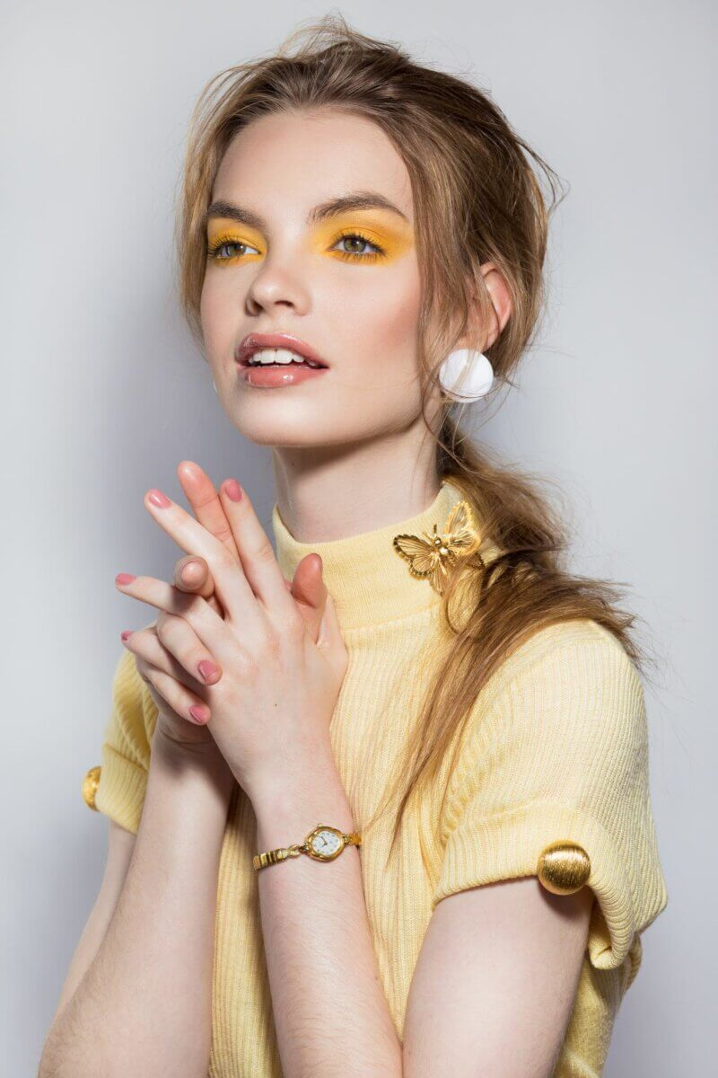 Retro meets radical as model wears light yellow sweater as well as bright yellow eyeshadow