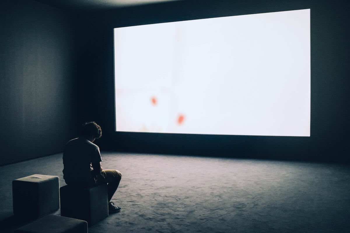 man sitting in small makeshift cinema in a Canadian art institution