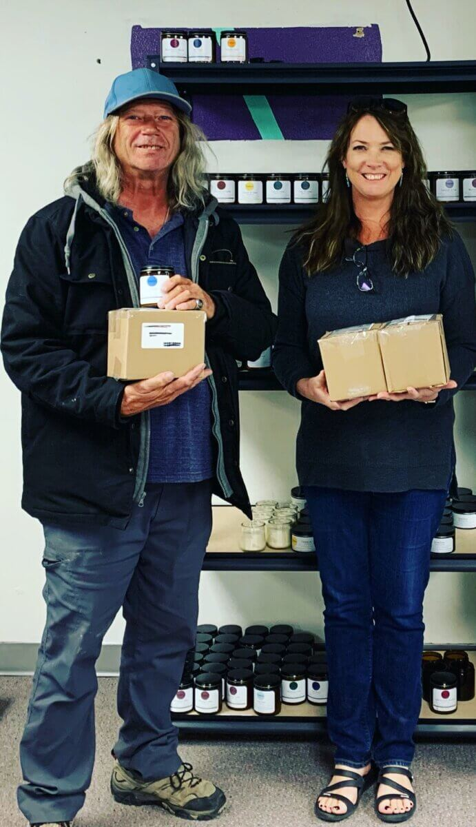 man and woman holding boxes of handmade candles, part of All in ADays Work program