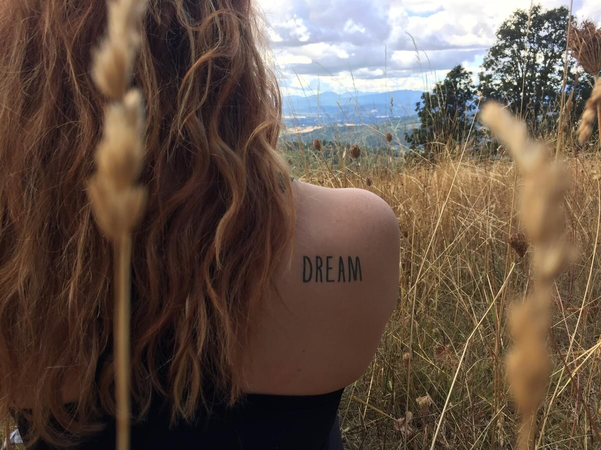 A conscious ink temporary tattoo on a woman's shoulder that says Dream