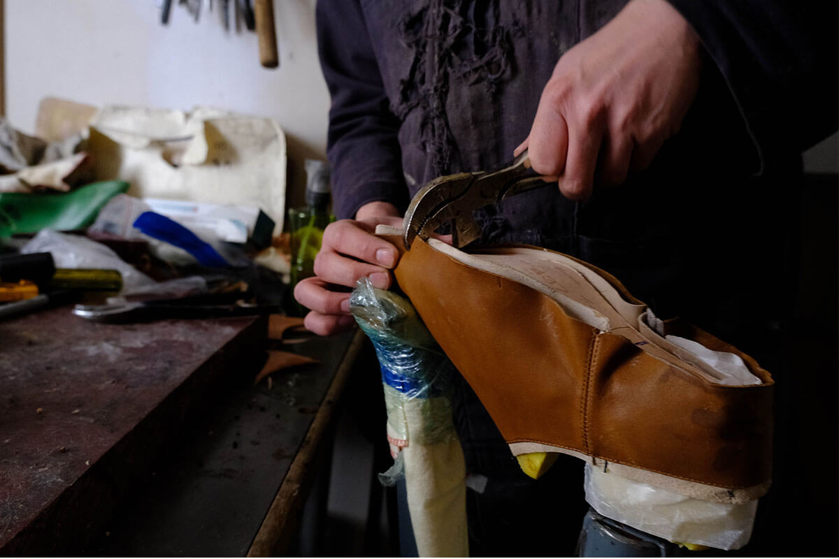 Adam Finn stretching the leather over the last of a pair of custom made shoes