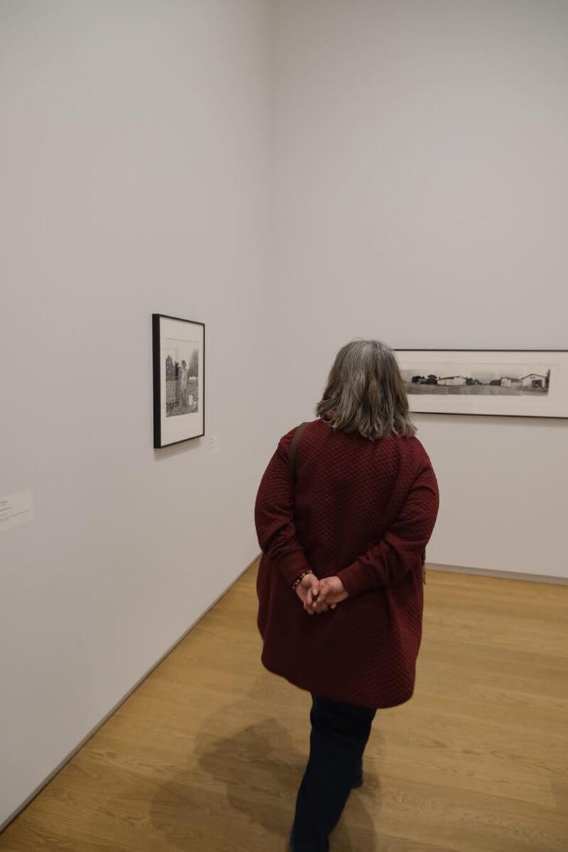 woman touring a back and white photo exhibit, explore Saskatoon in April