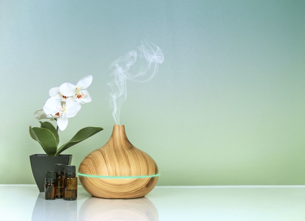 diffuser beside a white flower keeping fresh air in small spaces