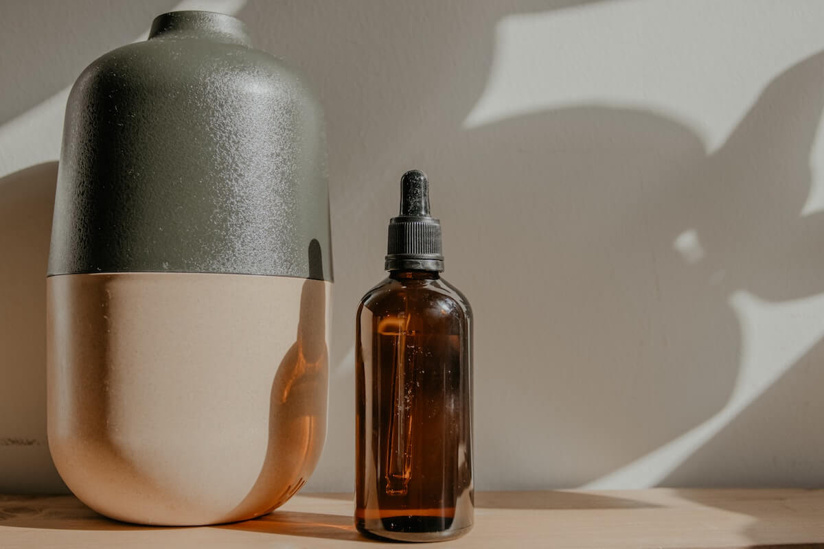 diffuser beside a bottle of essential oll to help keep fresh air in a small space
