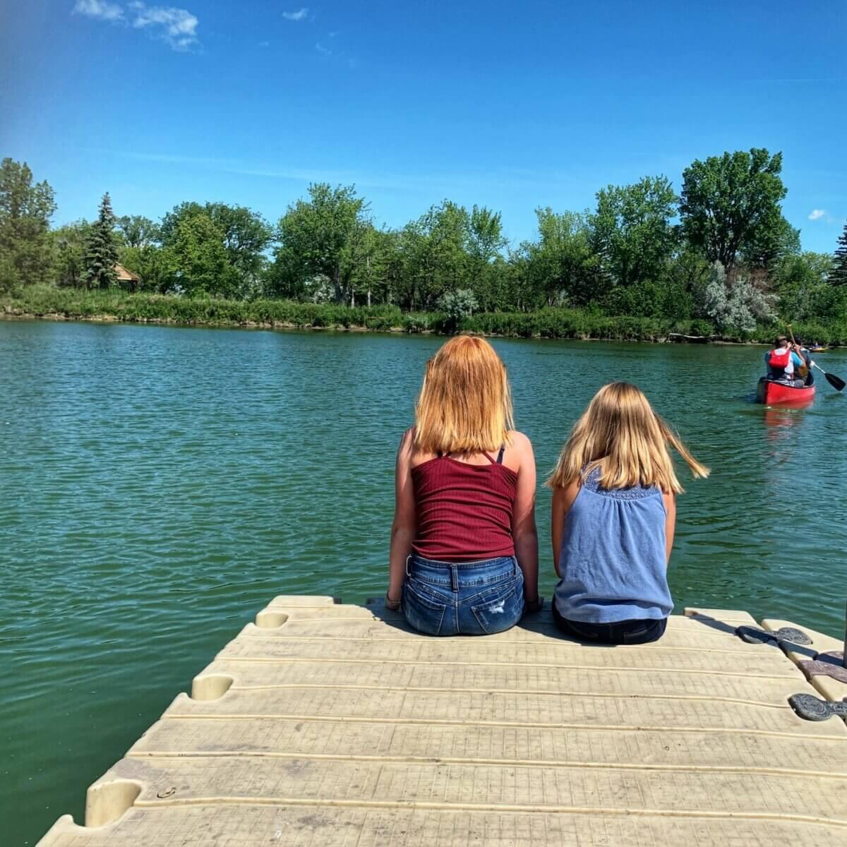 2 girls sitting on a dock