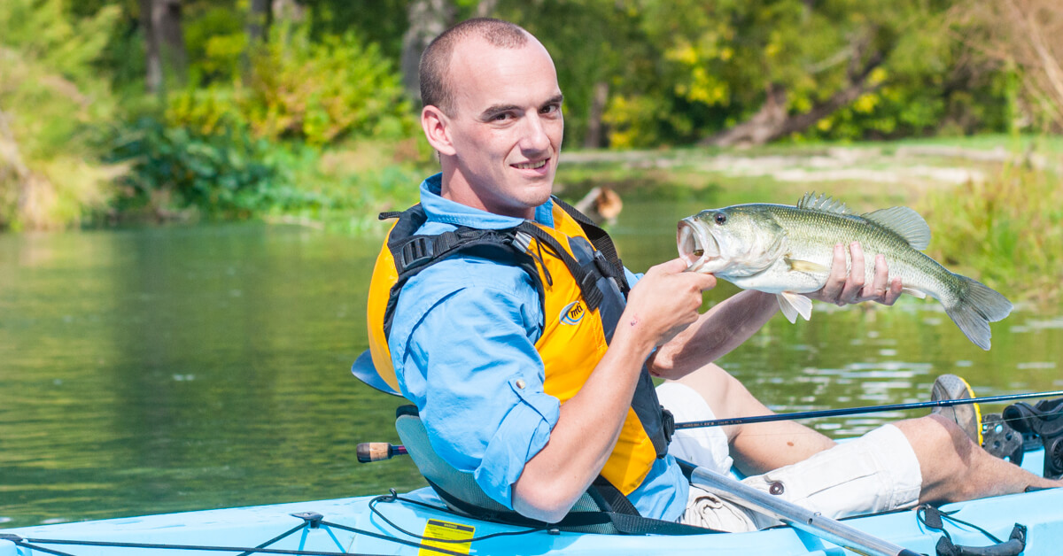 man in kayak holding a caught fish, part of Heroes on the Water