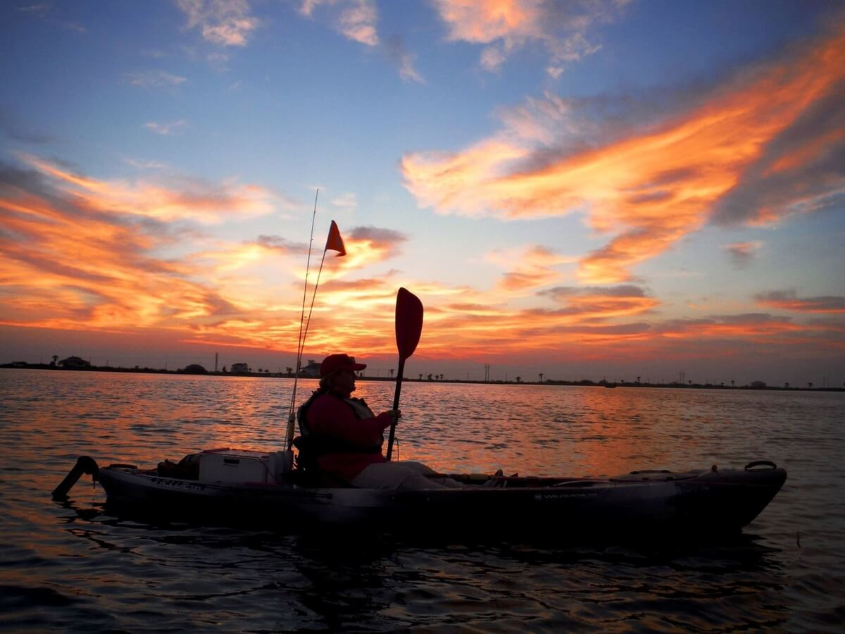 kayak fisherman at sunset on a lake