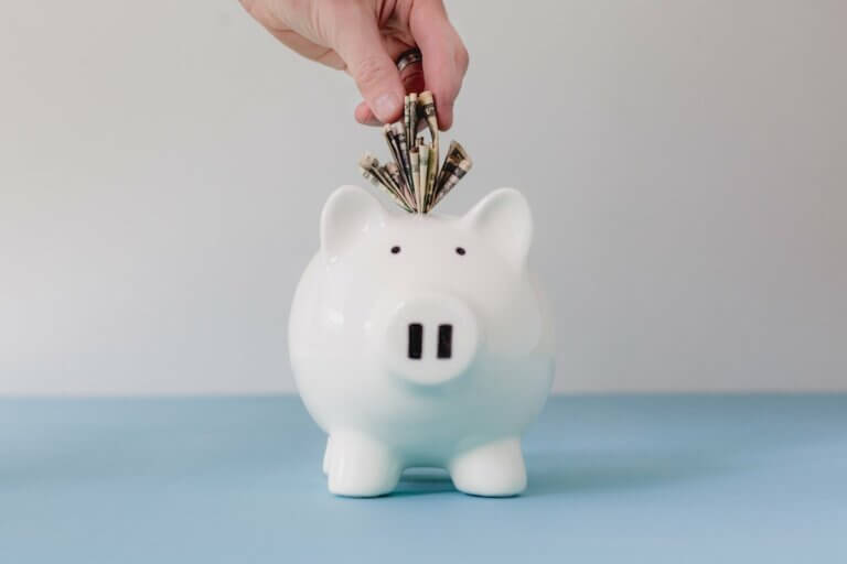 putting money in a white piggy bank to address your financial debt in a healthy way