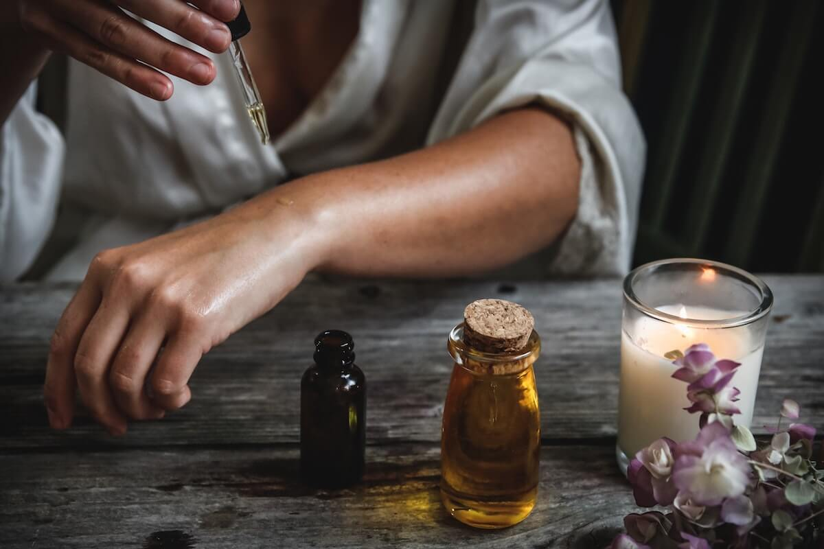 A woman putting essentials oils on her arm, one of 4 ways to get a better sleep