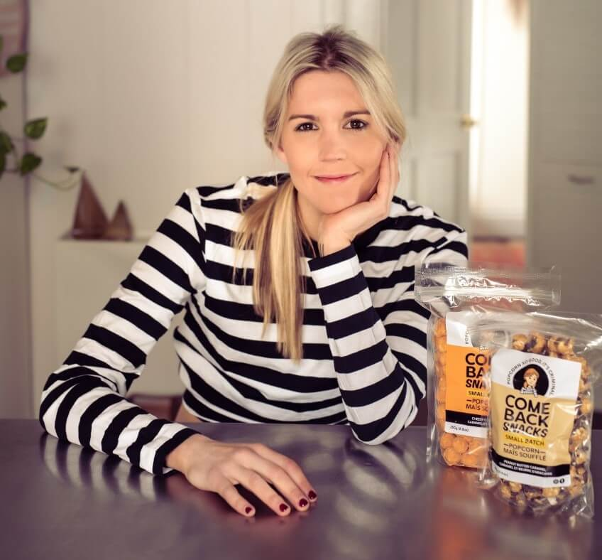 emily o'brien at a table with 2 bags of comeback snacks, popcorn with a mission