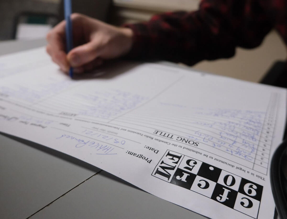 a man's hand on a song list sheet at the saskatoon community radio station