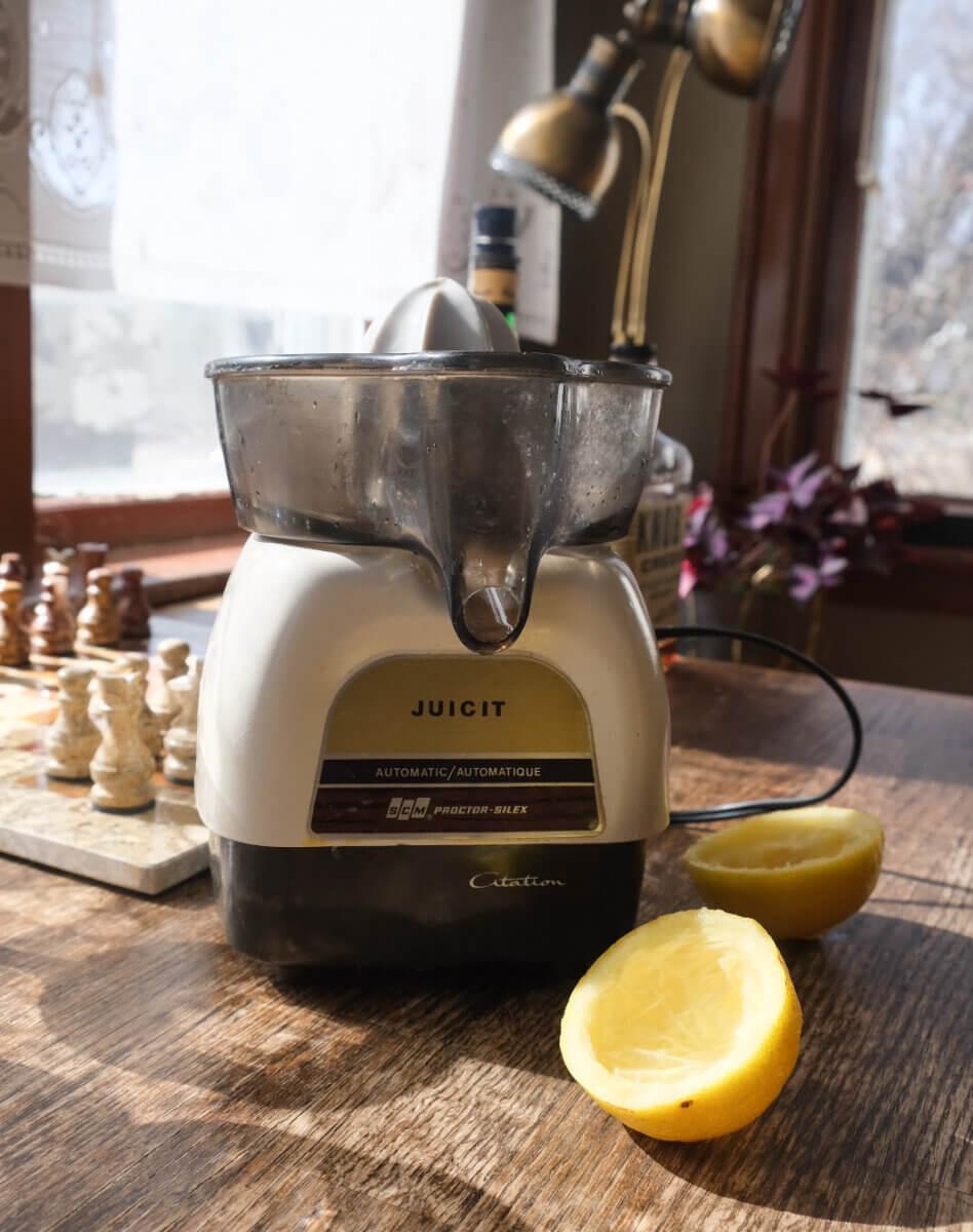 vintage juicer on a kitchen counter beside lemon halves