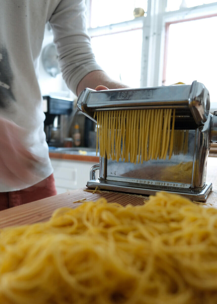a silver pasta roller producing noodles, a quality piece of secondhand kitchen equipment