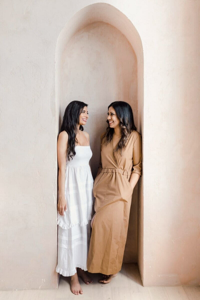 2 women in white and brown long dresses, smiling at each other
