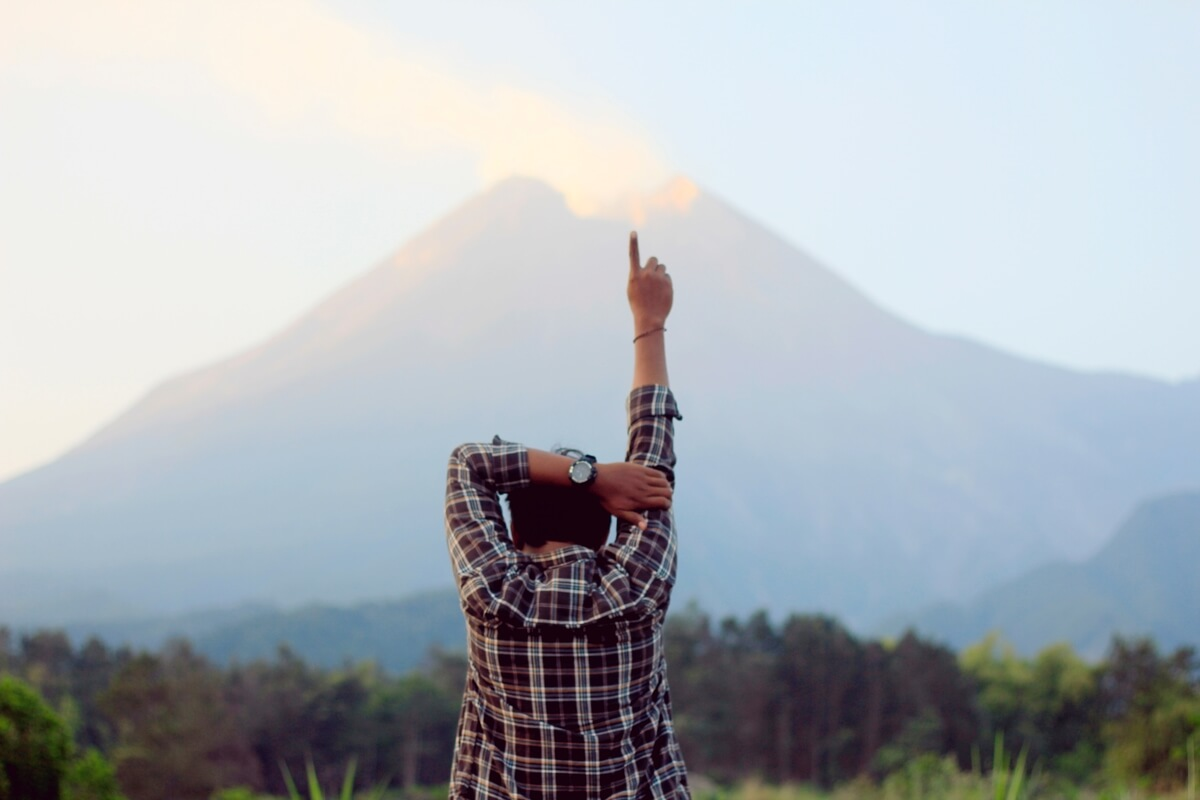 a man holding his hand up facing a mountain, the secret to unlimited possibilities