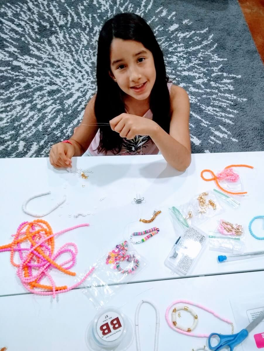 young girl making bracelets for shining brownies to help other kids