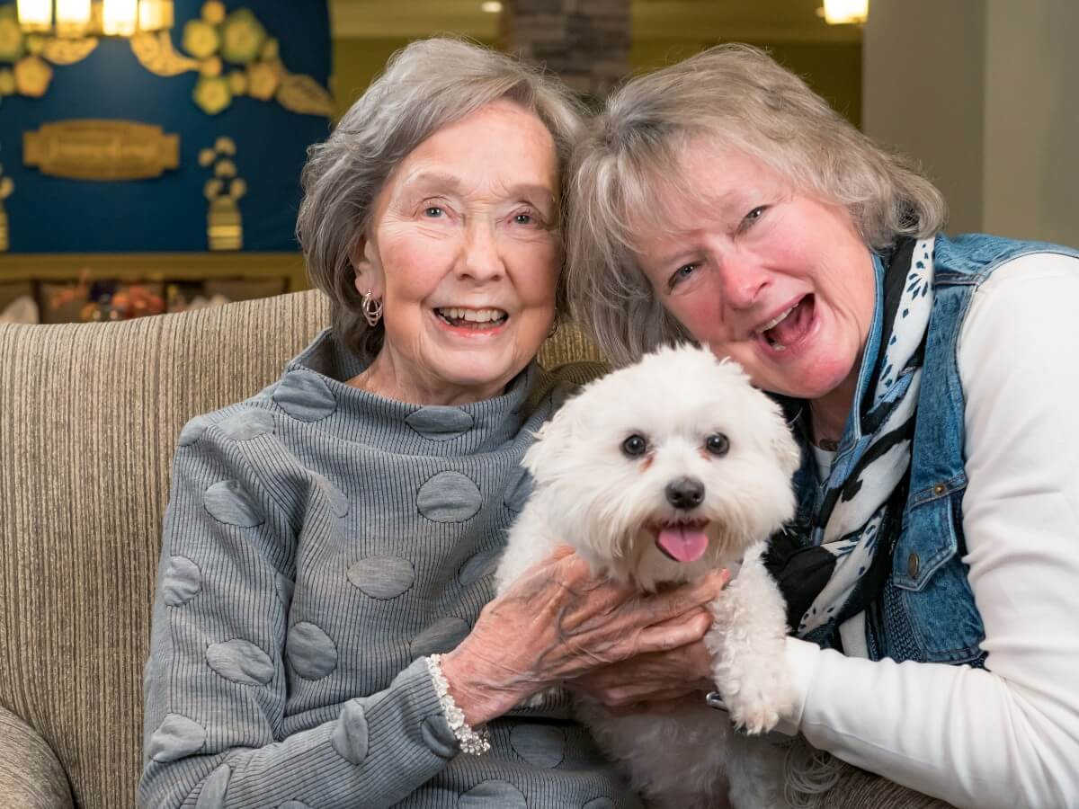 2 women with small white dog as part of doggies for dementia