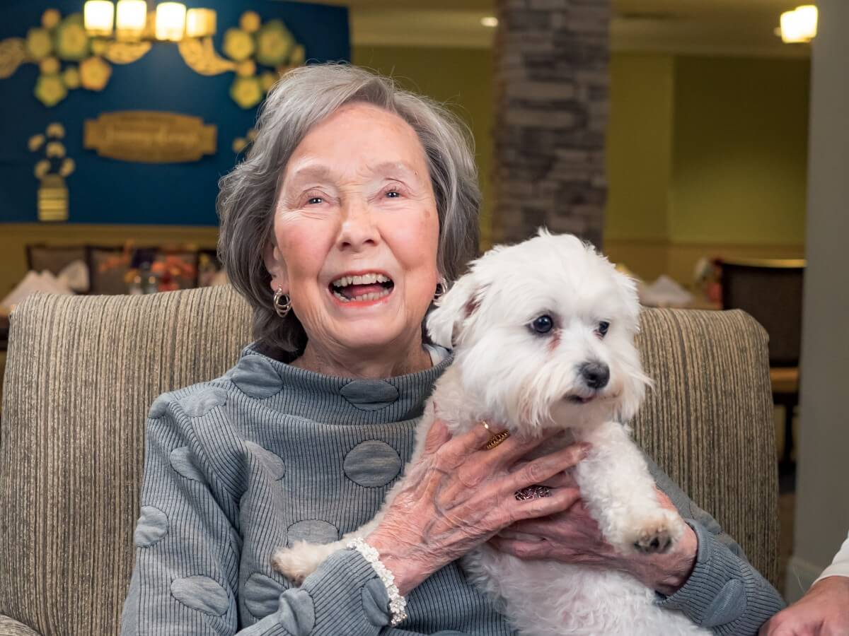 happy elderly woman holding her small white dog while doggies for dementia takes a photo
