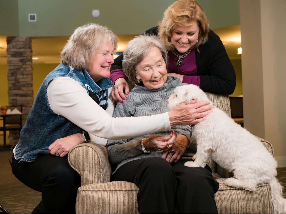 2 women with their mother adoring a small white dog