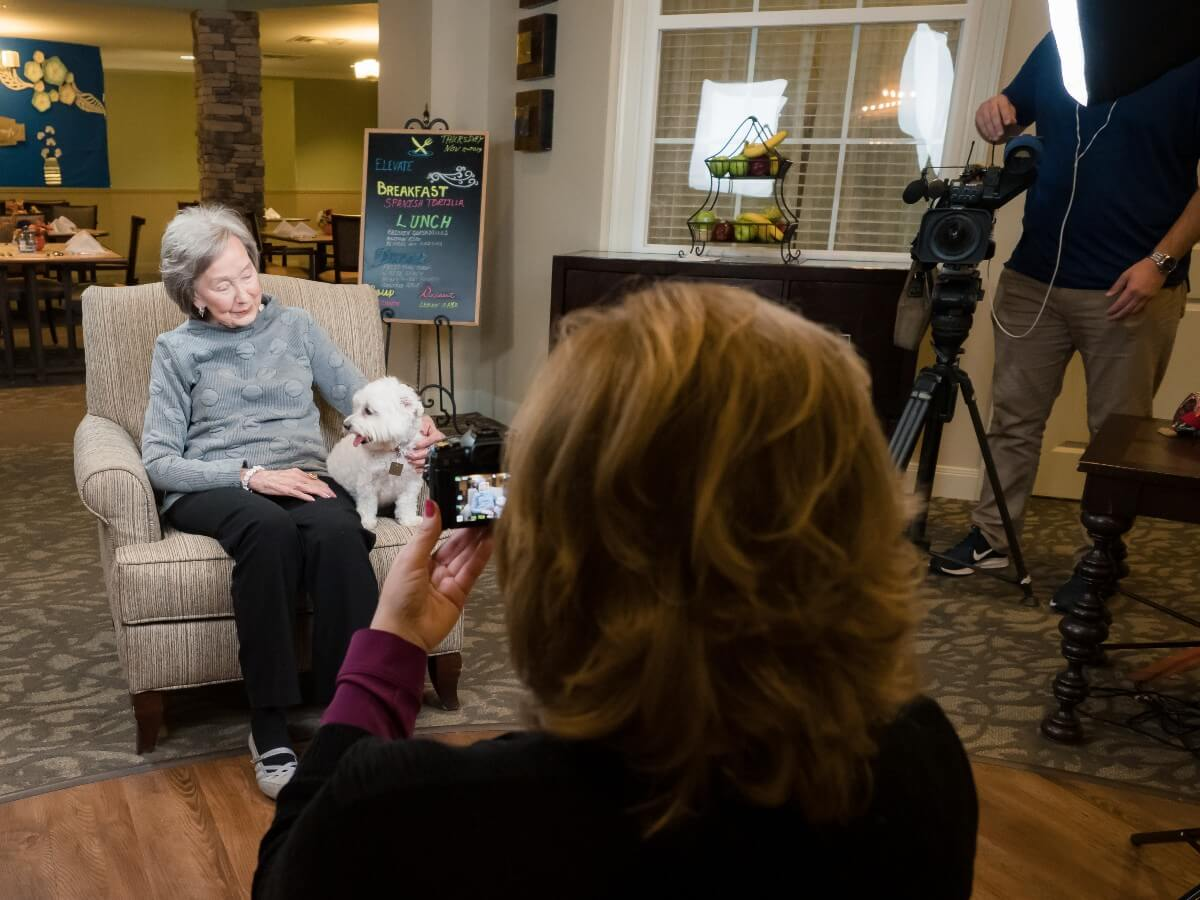 doggies for dementia taking photos of an elderly woman with her small white dog