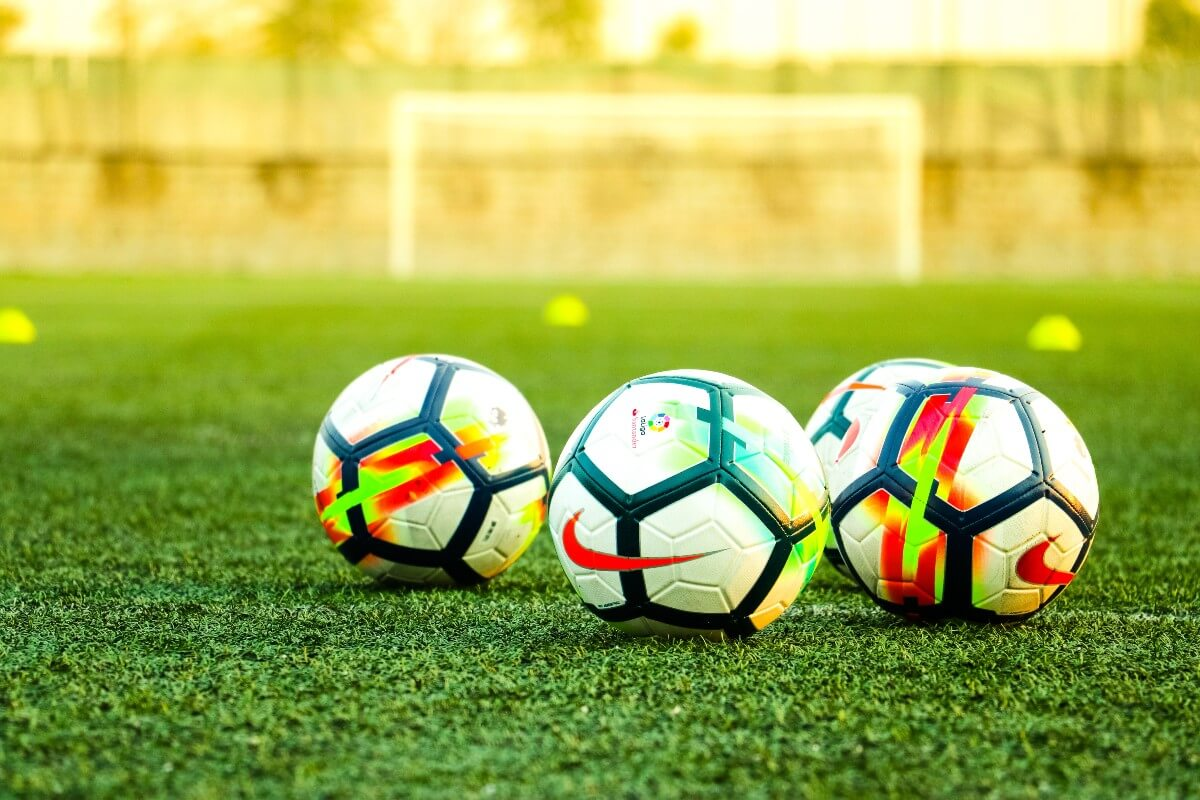 4 soccer balls on a pitch used for for grassroots soccer