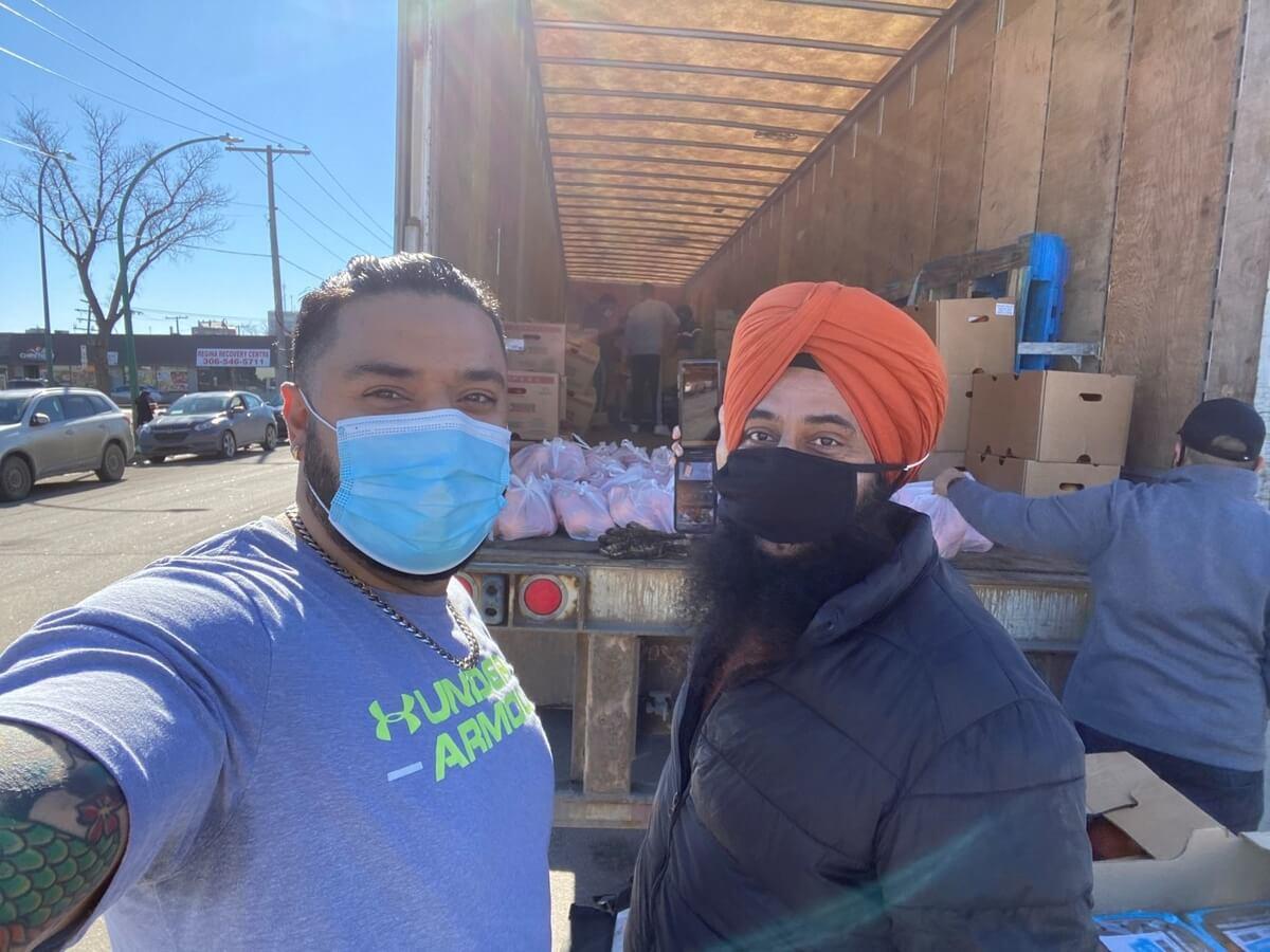 Volunteers loading food onto a large truck for Guru Nanak Free Kitchen