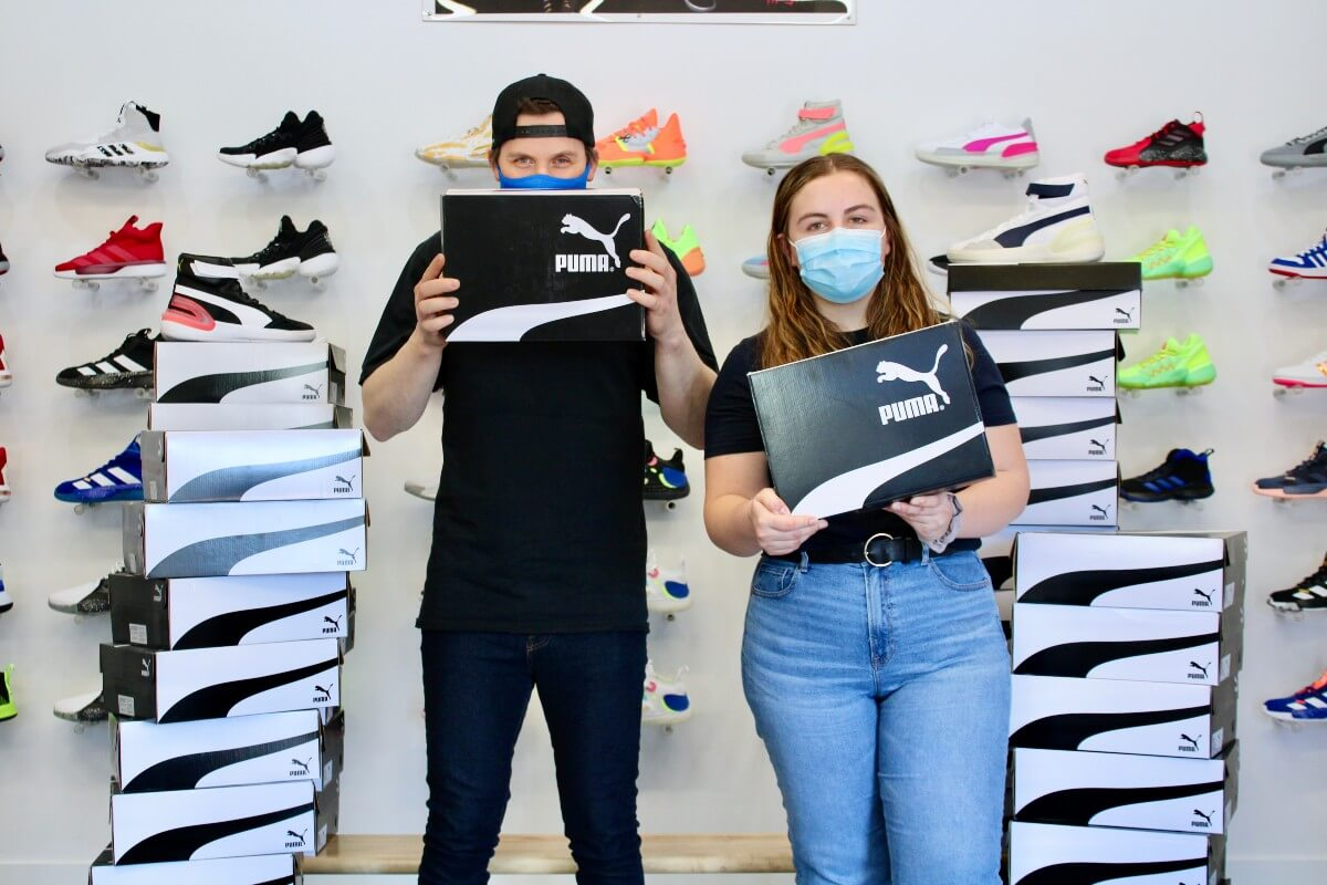 2 young people at John Howard Society beside donation of PUMA shoes