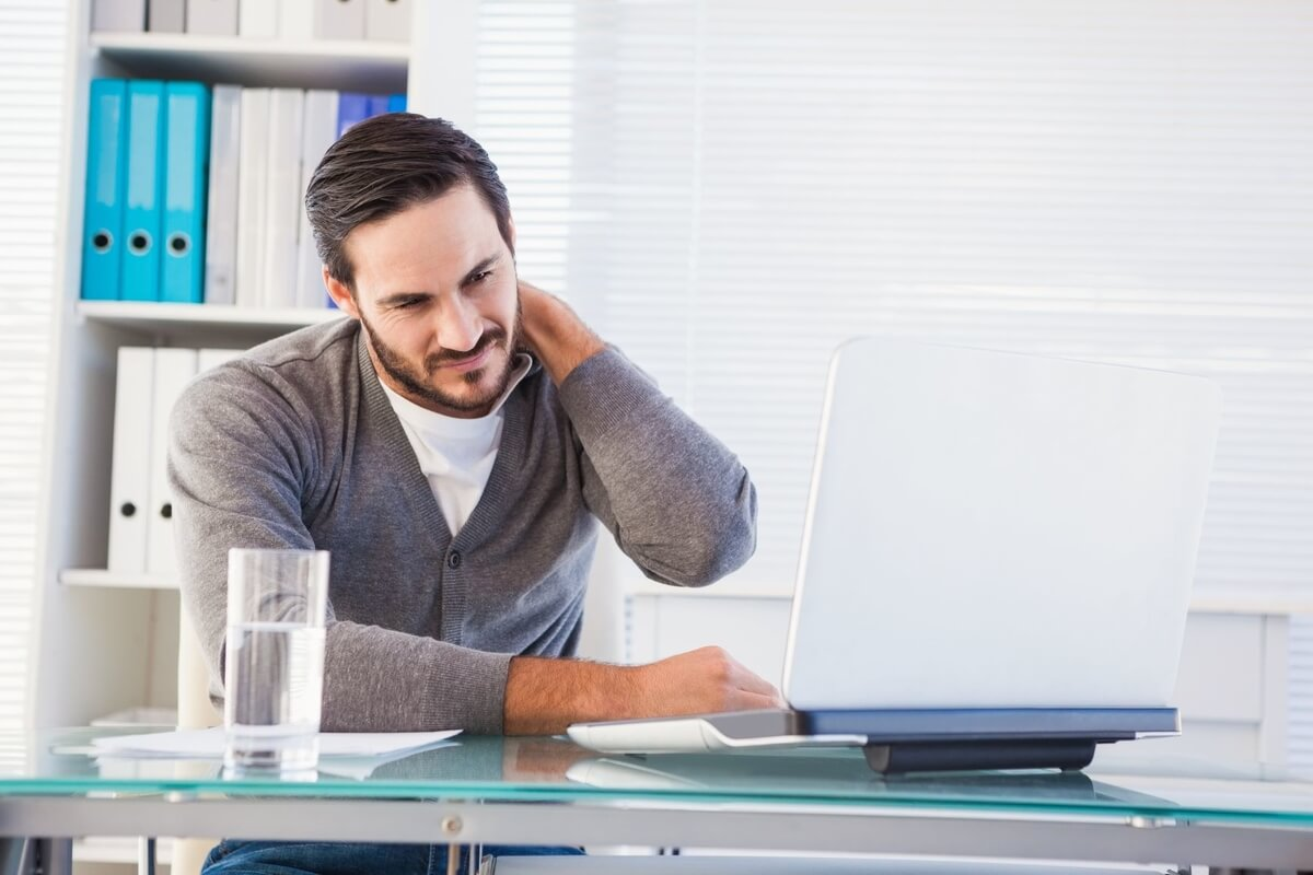 man working at desk with sore neck needing massage tools