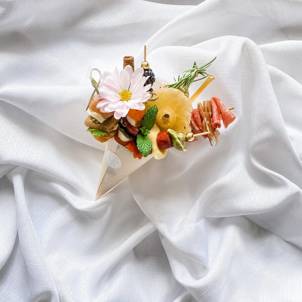 a colourful appetizer cone with flowers on a white sheet