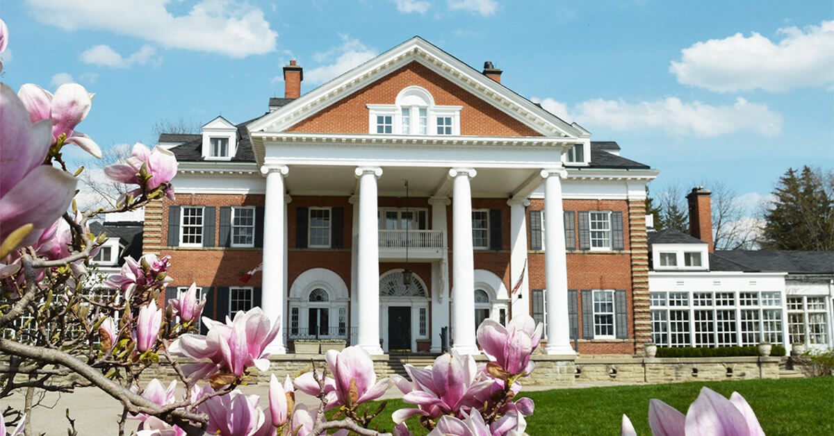 elegant brick and white country house and spa with pink apple blossoms in foreground