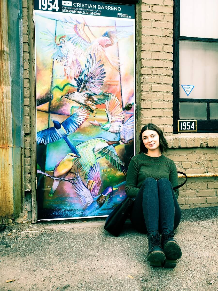 woman sitting beside a mural in Regina's Cathedral community