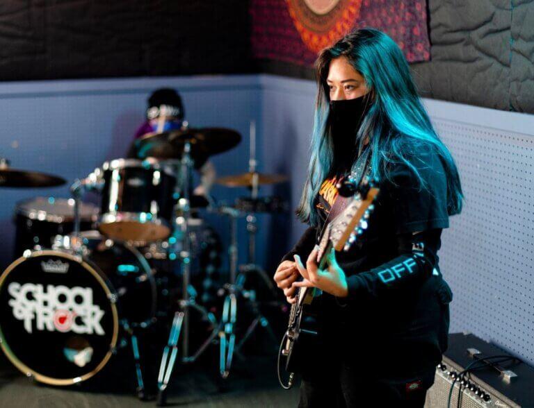 woman pn electric guitar near a drummer at regina's school of rock