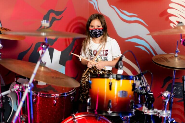 young girl playing drums at regina's school of rock