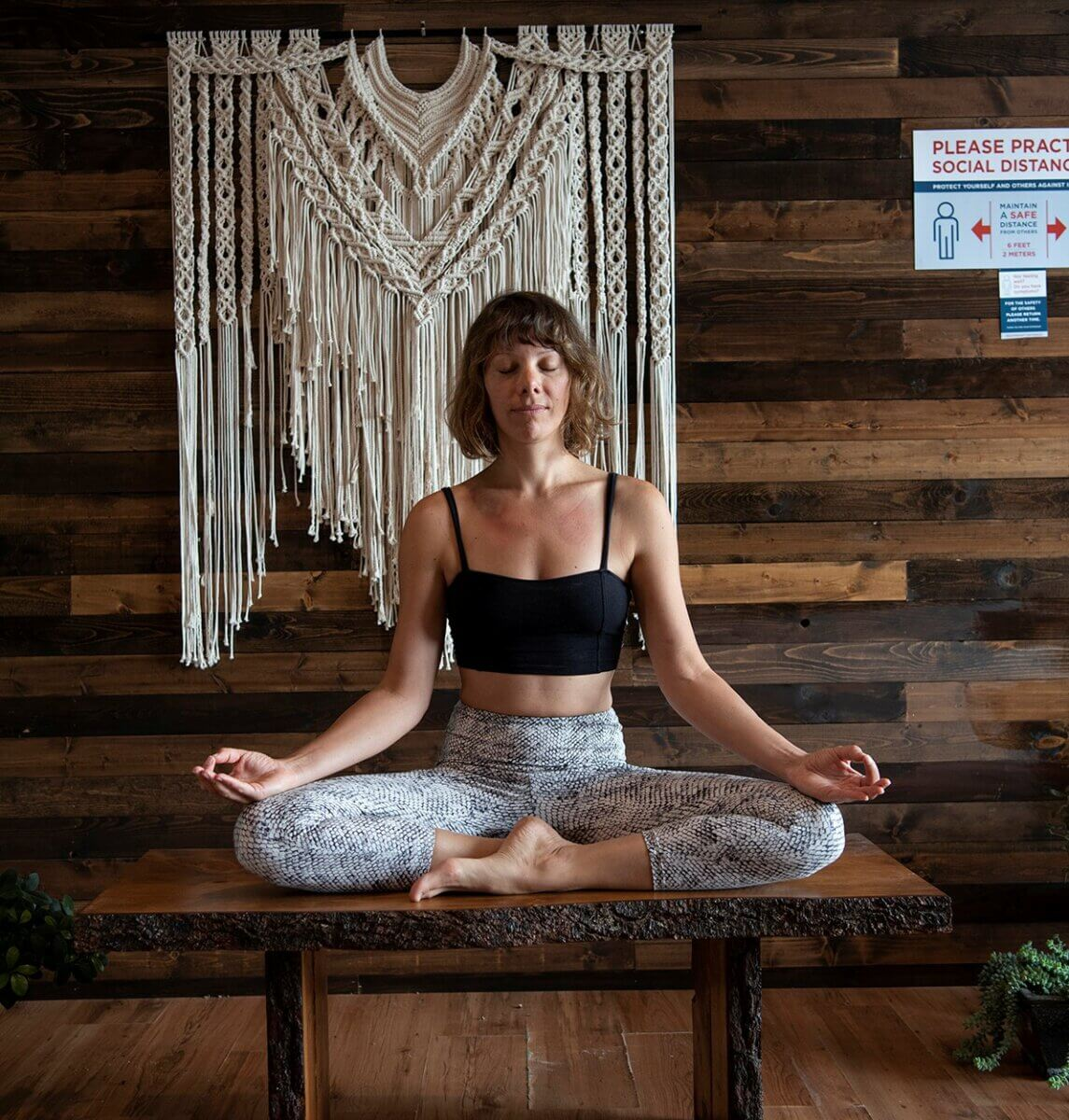 A woman meditating on a wooden bench with a macrame hanging behind her