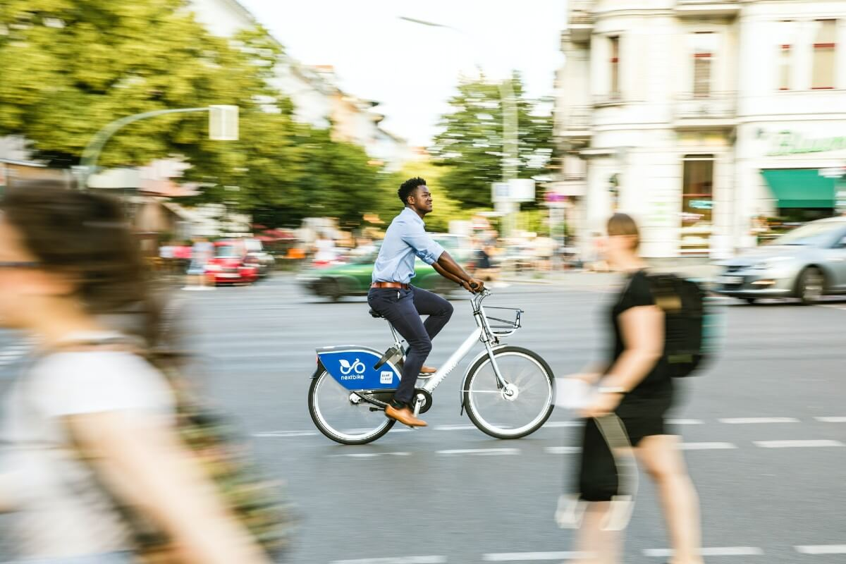 man riding a bike in a city to reduce carbon and help save the oceans