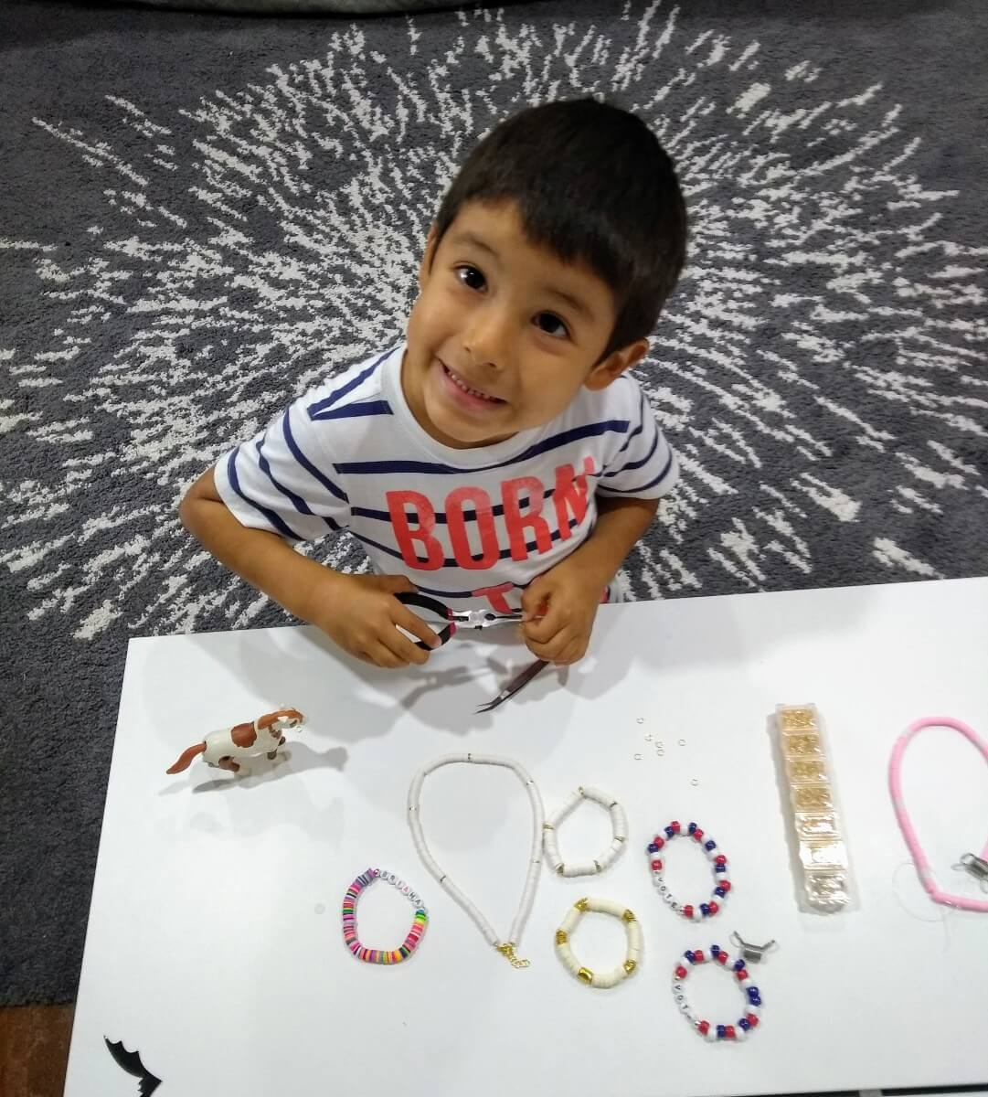 young boy making bracelets for shining brownies to help other kids