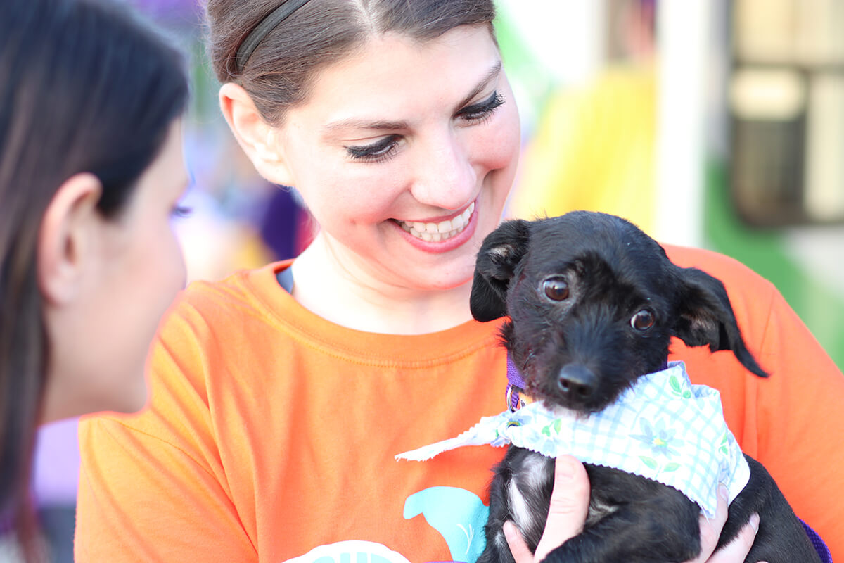 woman in orange shirt holding small black dog participating in the Strut Your Mutt event