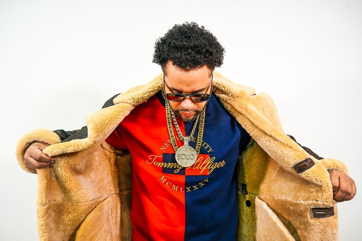 black man in brown winter jacket and red and blue Tommy Hilfilger sweatshirt