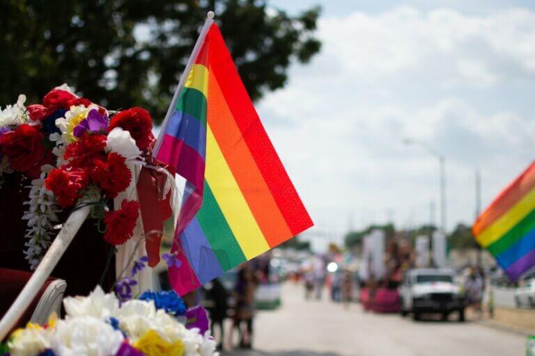 pride flag flying at a parade