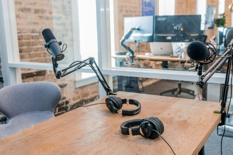 headphones, microphone and computers for Dear Media podcasting