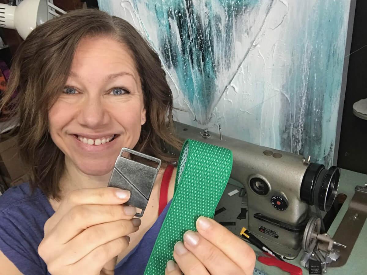 Renia Pruchnicki, owner and product designer of Truth Belts, holding up a green vegan belt