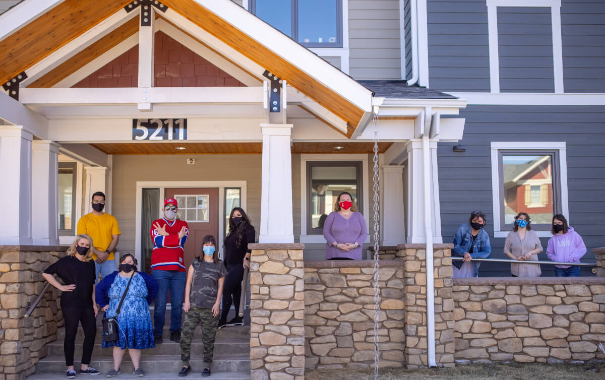 people standing in fornt of a house at creative options regina