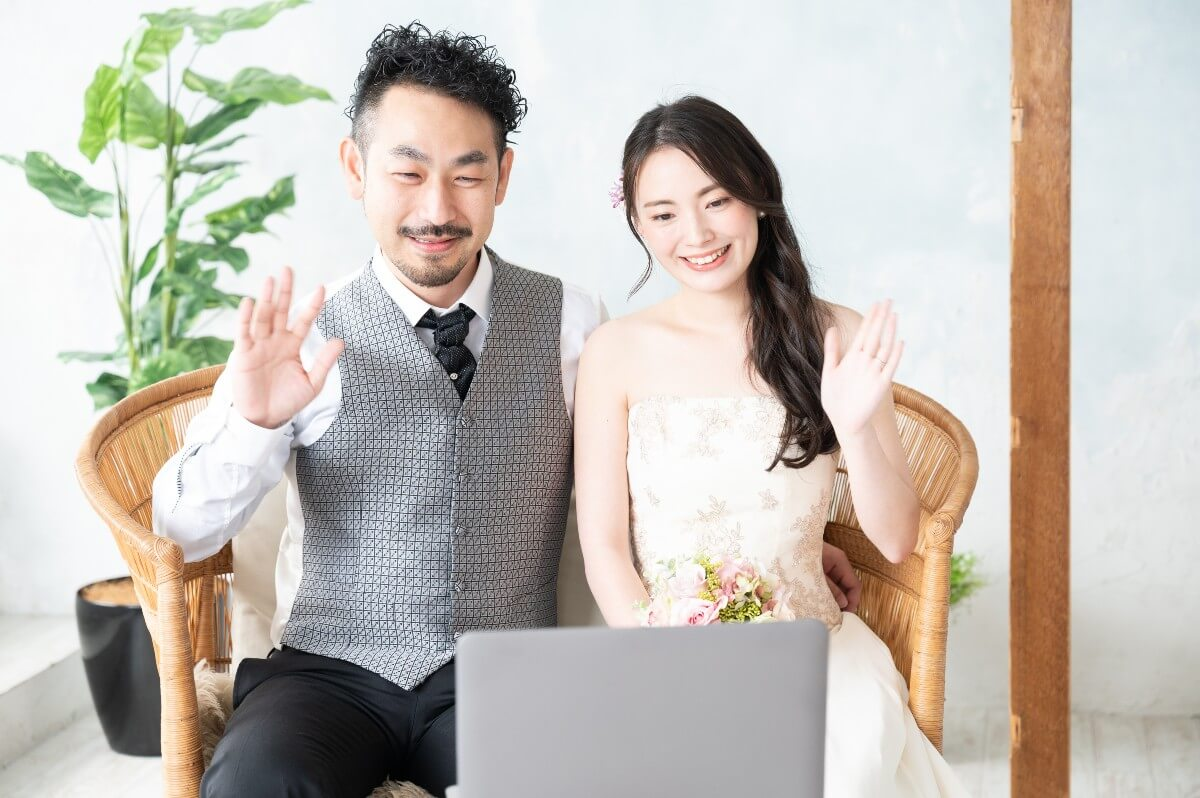 wedding couple waving at a laptop using Zoom