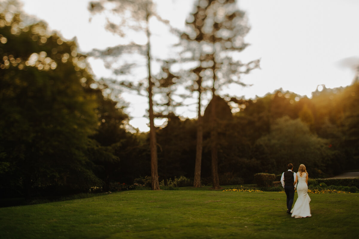 a man and woman walking at their outdoor wedding