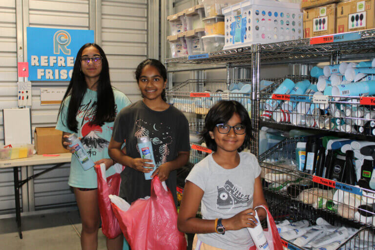 3 young girls benefiting from refresh frisco donates hygiene products