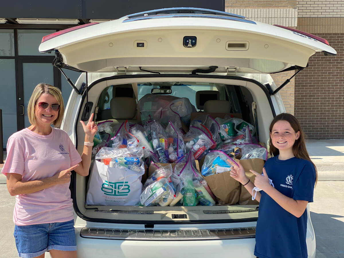woman and young girl beside a vehicle full of hygiene products donated by Refresh Frisco